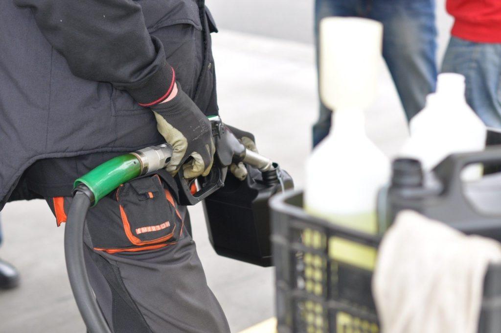 Mężczyzna w roboczym stroju, tankujący paliwo do małego czarnego kanistra.