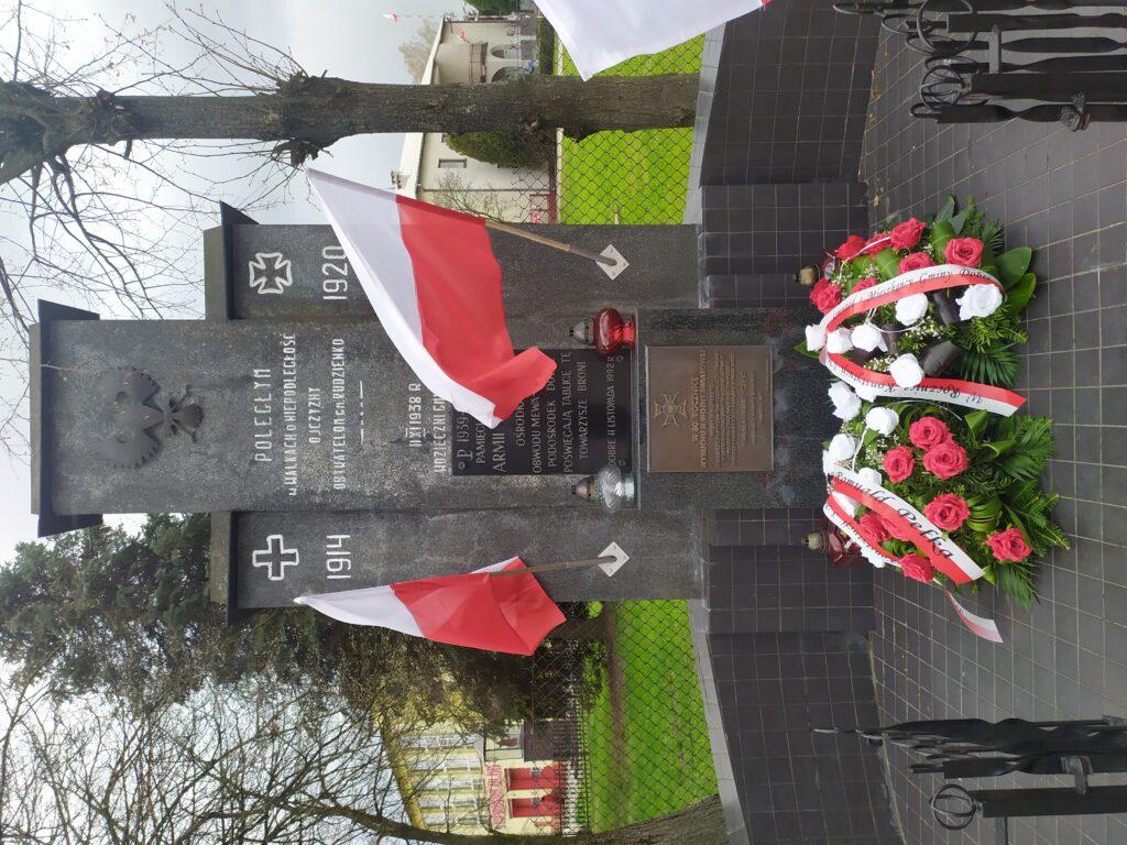 Pomnik z 1938r. udekorowany kwiatami oraz biało-czerwonymi flagami.