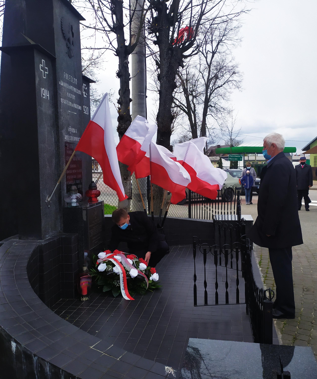 Dwaj mężczyźni przed pomnikiem. Jeden z nich składa kwiaty. W tle biało-czerwone flagi.