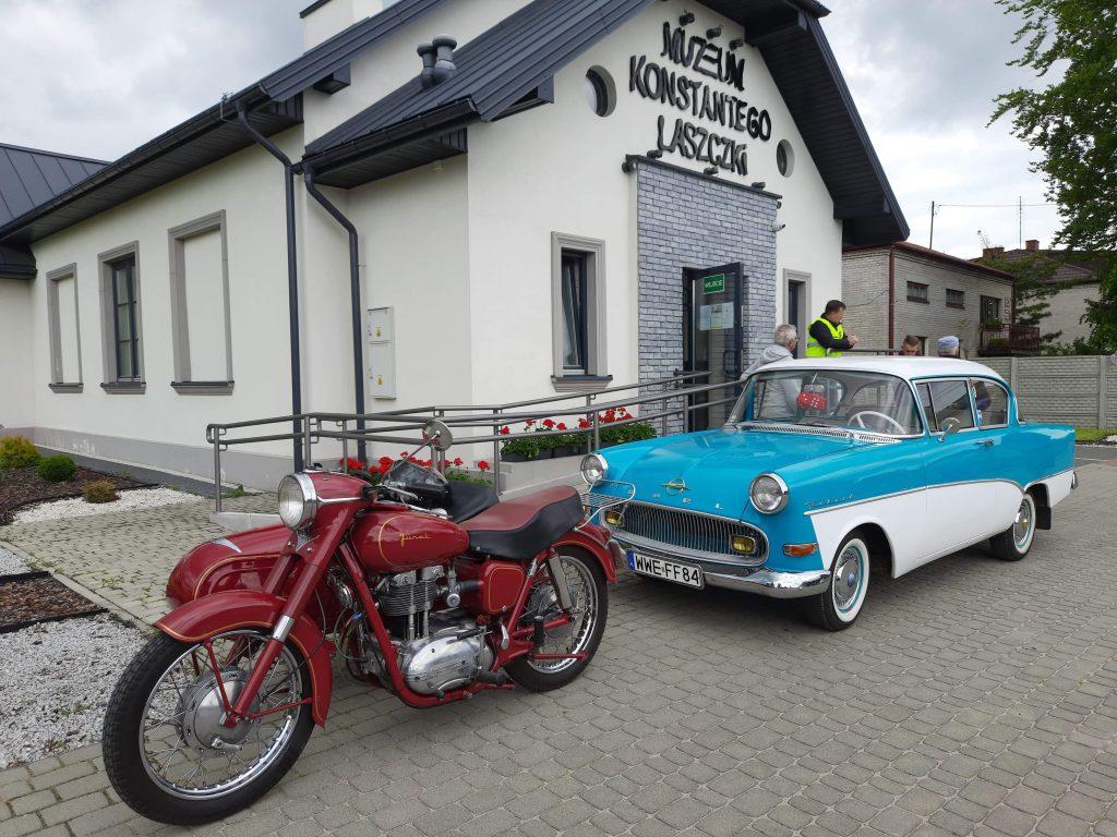 Zabytkowy samochód oraz motocykl, w tle biały budynek