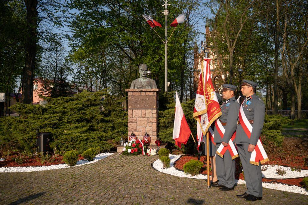 Z lewej strony trzy osoby w mundurach Piłsudczyków. W oddali pomnik-popiersie Piłsudskiego.