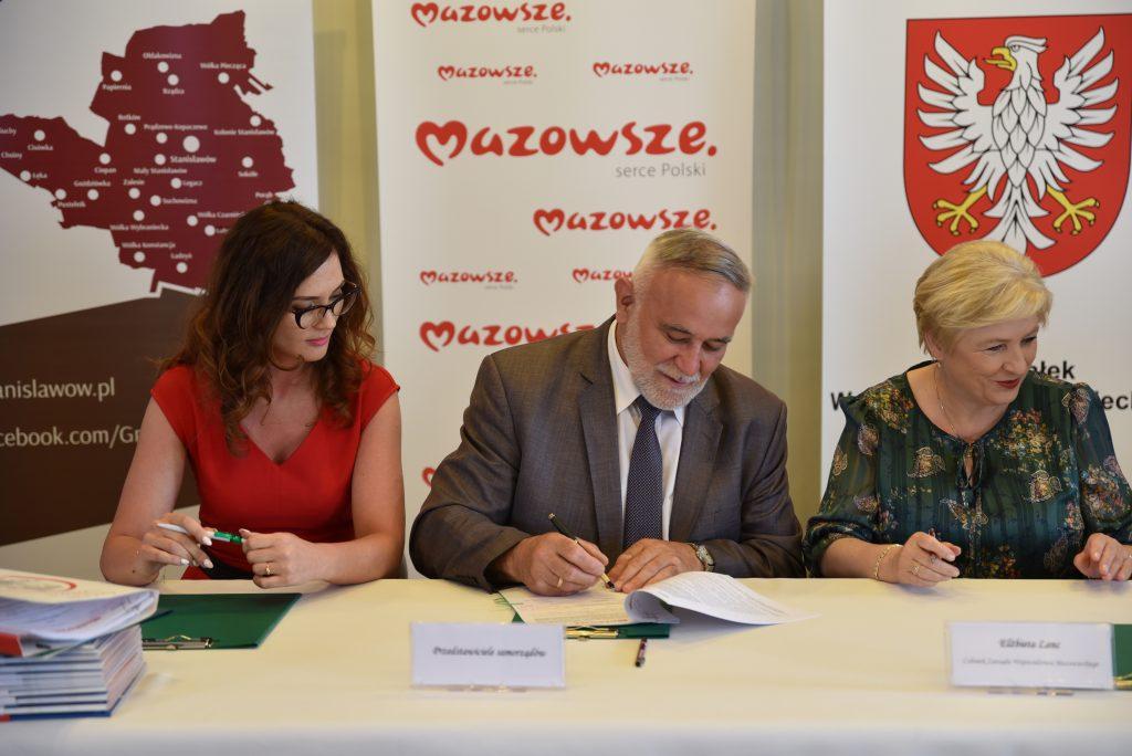 Trzy osoby siedzące przy stole. Mężczyzna z brodą w środku - podpisuje dokument, z lewej kobieta w czerwonej sukience, z prawej kobieta z jasnymi włosami.