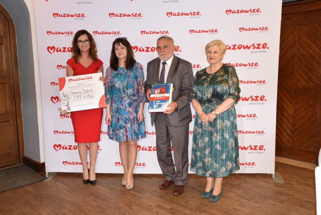 4 osoby stojące na tle ścianki - z czerwonymi napisami Mazowsze.