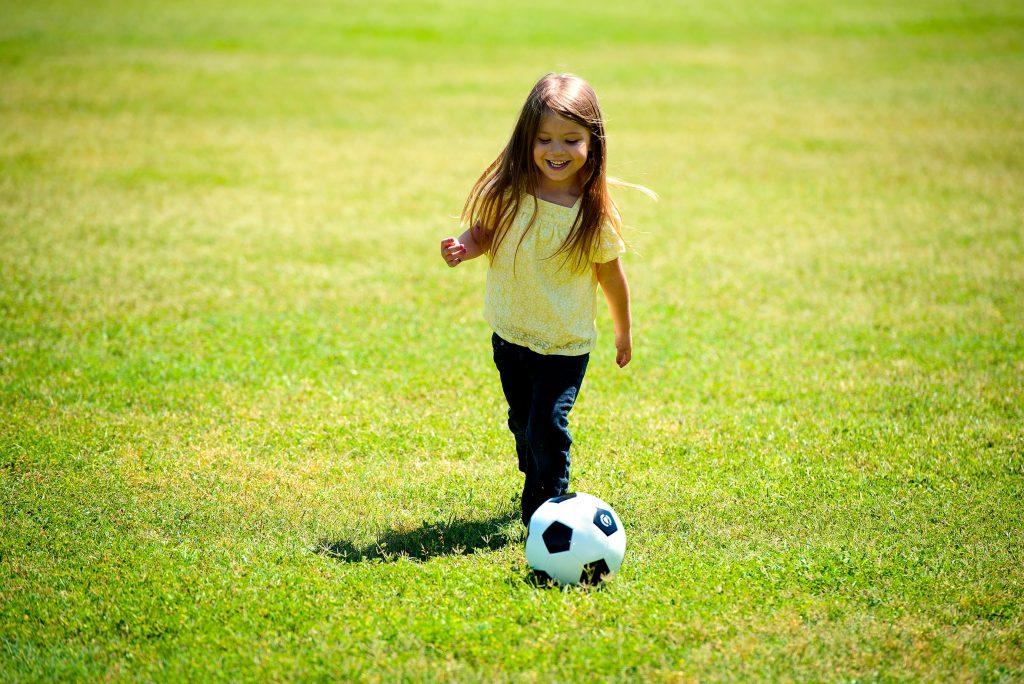 Kilkuletnia dziewczynka z piłką na trawie