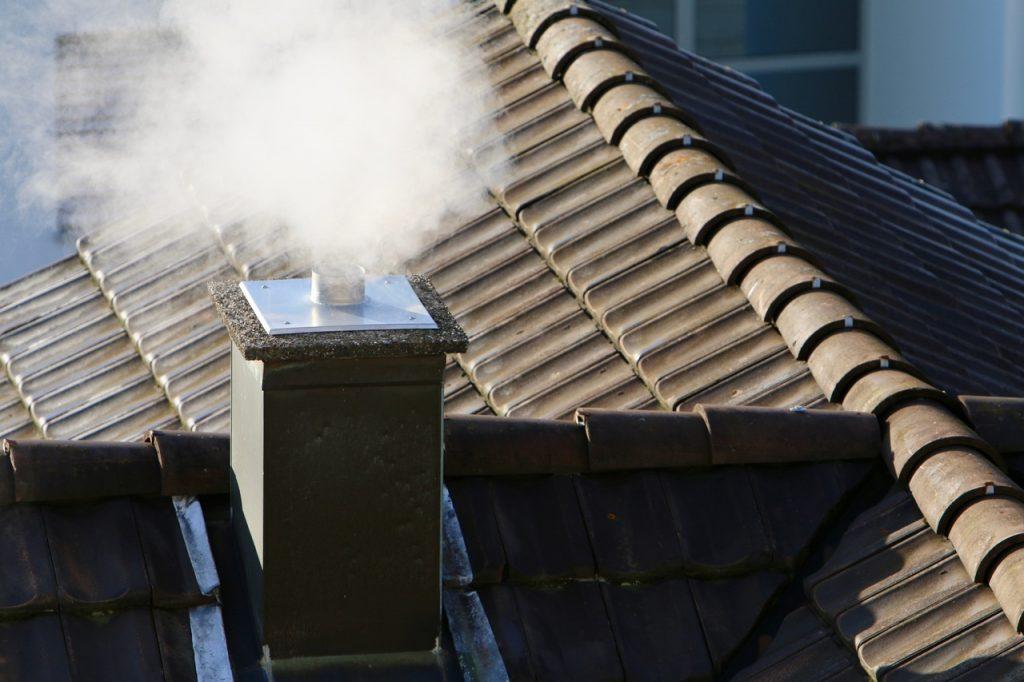 Dach i komin domu widoczny z góry. Z komina leci dym.