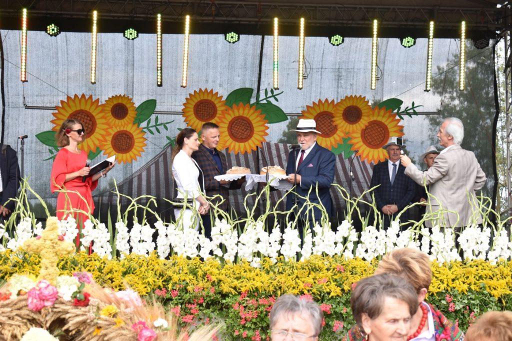 Scena ozdobiona kwiatami, na scenie 3 mężczyzn oraz kobieta