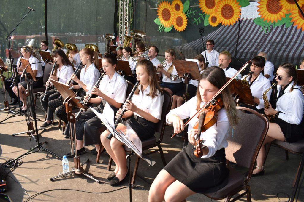 Członkowie orkiestry dętej grający na scenie