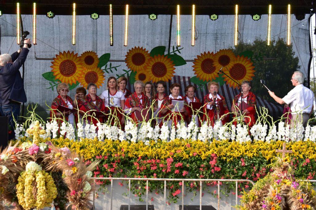 Kilkanaście kobiet w czerwonych strojach na scenie