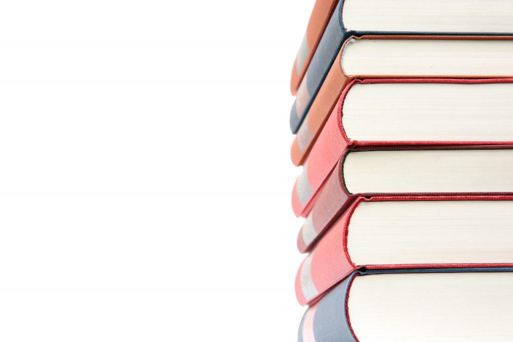 Z prawej strony stos książek , białe tło