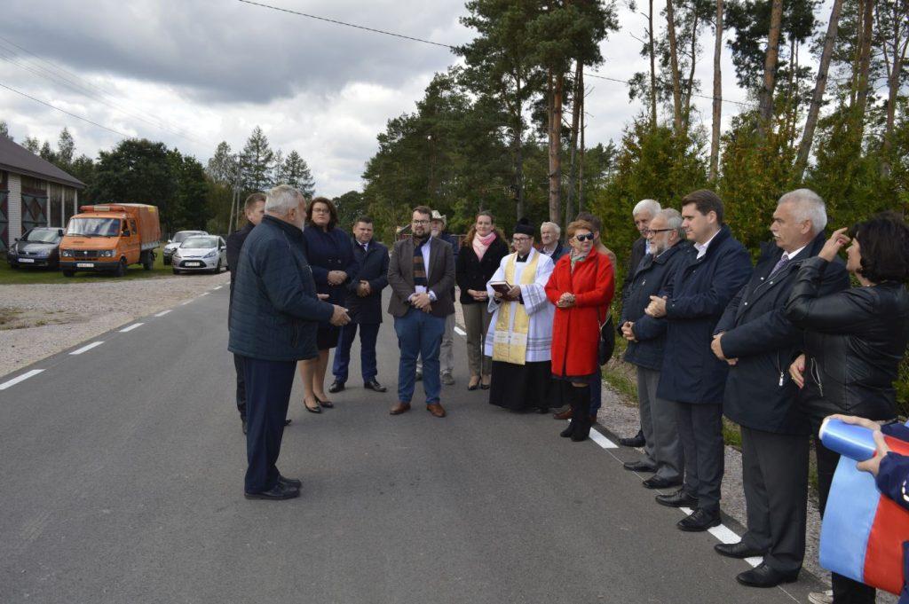 Kilkanaście osób stojących na drodze