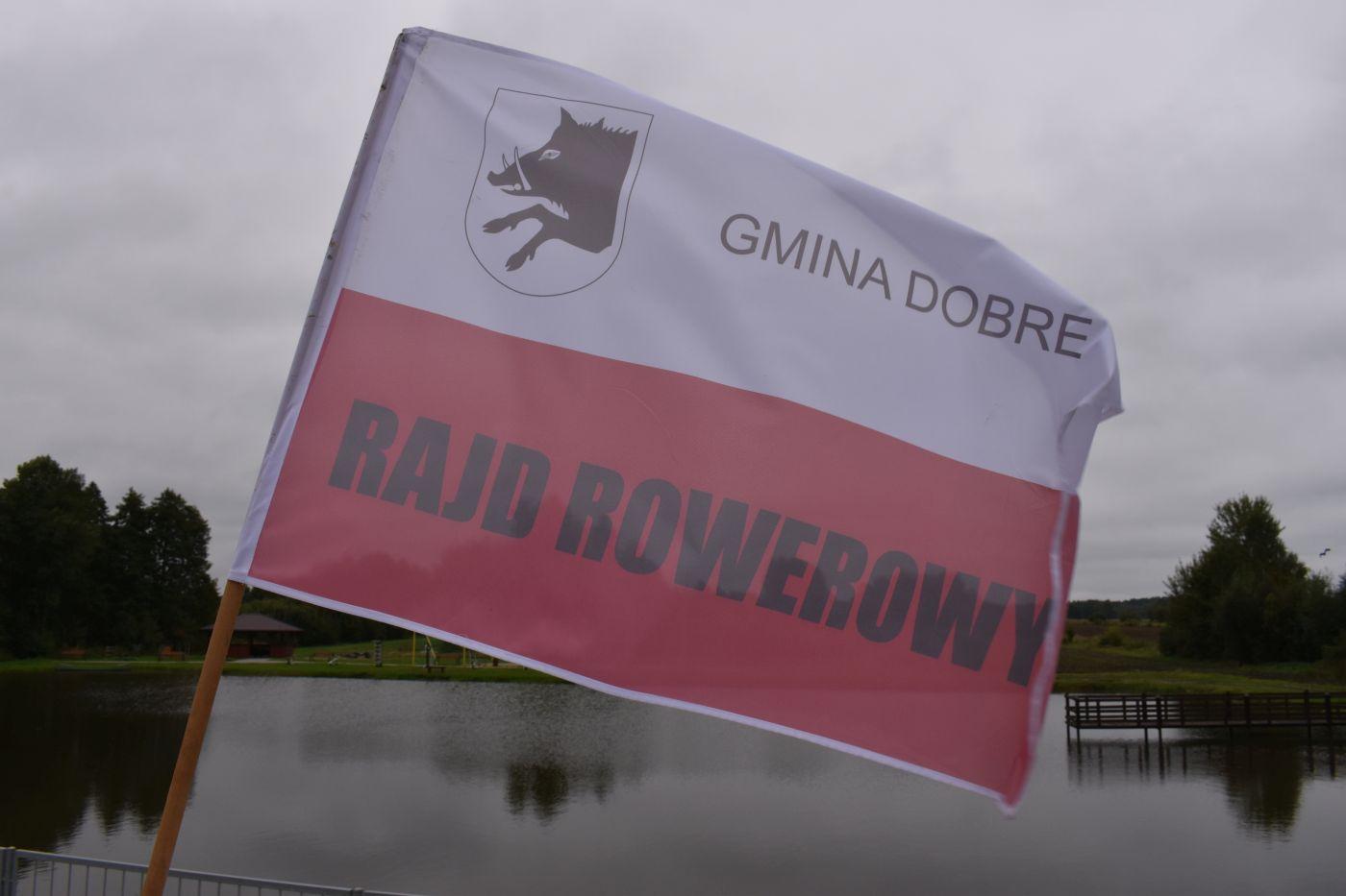 Flaga biało – czerwona na której jest herb przedstawiający głowę dzika i napis Gmina Dobre Rajd Rowerowy, w tle staw oraz drzewa.