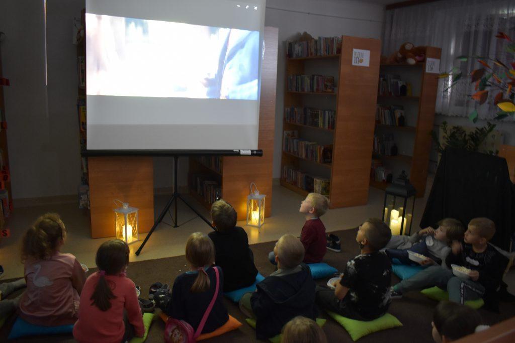 Grupa dzieci siedzi na wykładzinie, oglądają film, w tle regały z książkami i świecące lampiony