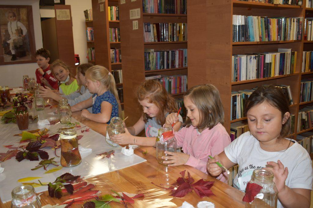 Kilkoro dzieci siedzi przy stole, malują pędzelkami po szklanych słoikach, w tle regały z książkami, i na stole kolorowe liście.