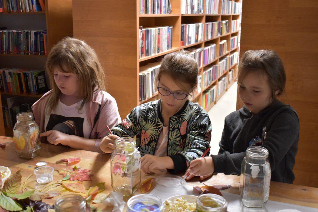 Trzy dziewczynki malują słoiki i przyklejają na nich kolorowe liście, za nimi stoją regały z książkami.