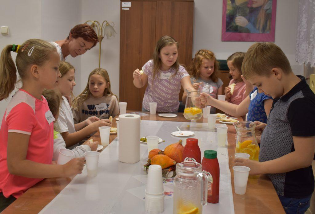 Gromadka dzieci je przy stole, chłopiec nalewa sobie picie, dziewczynka trzyma w ręku biały plastikowy kubek. Na stole leży biały obrus, leżą małe dynie stoją keczupy, kubeczki i dzbanki.