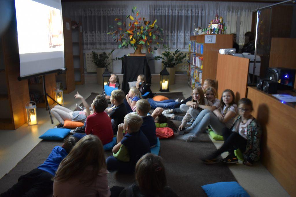 W sali przed ekranem na kolorowych poduszkach siedzą dziewczynki i chłopcy. W oddali widać świecące lampiony i kwiaty