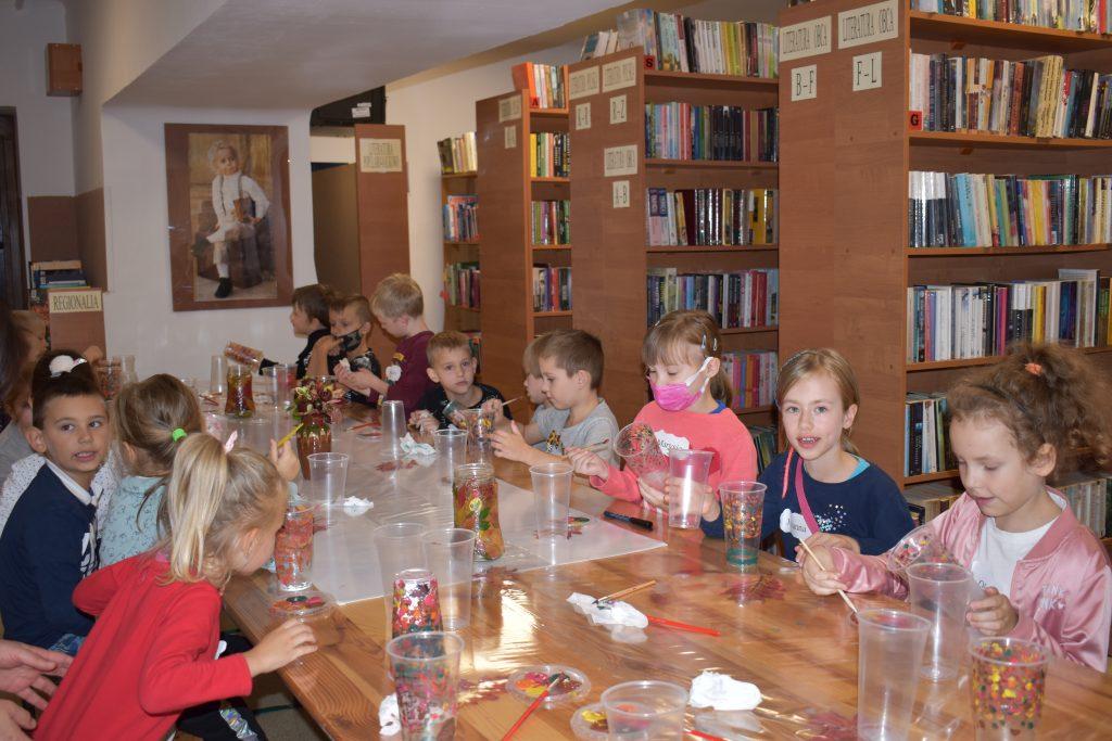 Przy długim stole siedzą dzieci, które malują farbami plastikowe kubeczki. W tle regały z książkami