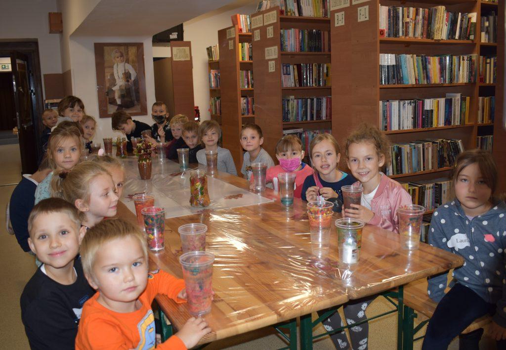 Zadowolona gromadka dzieci siedzi przy stole, w ręku trzymają plastikowe kubeczki pomalowane w barwy jesieni. W tle półki pełne książek.