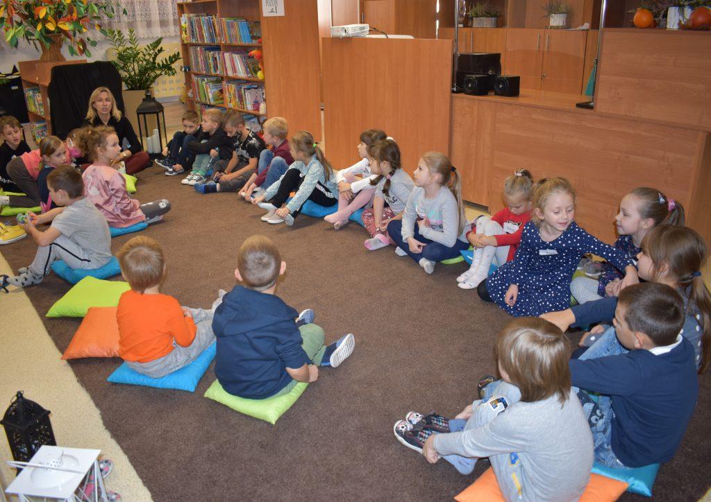 W sali bibliotecznej na kolorowych poduszkach siedzą dzieci i słuchają pani która do nich mówi. W tle regały i półki z książkami oraz kwiaty.