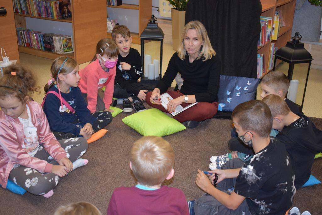 Pani czyta dzieciom, siedzącym na dywanie, za nią stoją lampiony i regały z książkami.