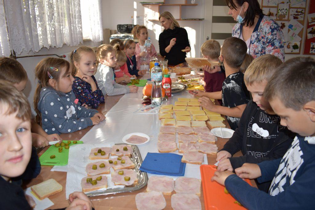 Grupa dzieci przygotowuje kanapki, na stole jest wędlina i ser, chłopcy kroją ogórki.
