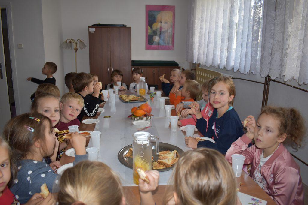 Grupa zadowolonych dzieci siedzi przy stole jedząc kanapki i piją wodę.