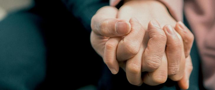 splecione ręce w uścisku na ciemnym tle