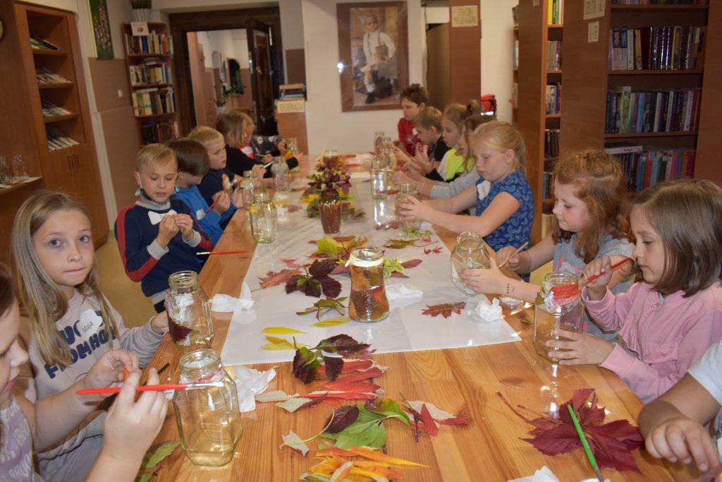 Przy drewnianym stole, na którym leżą kolorowe liście siedzą dzieci i malują pędzelkami po szklanych słoikach. W tle regały z książkami.