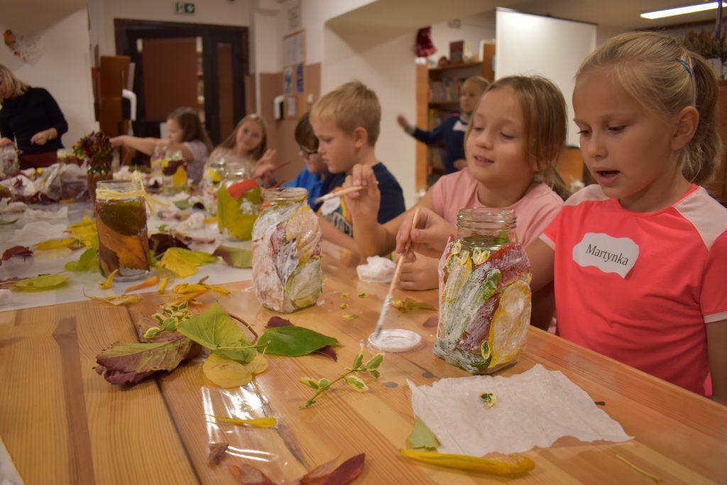 Dzieci siedzą przy stole i malują pędzelkami. Na stole stoją szklane słoiki na których są poprzyklejane kolorowe liście.