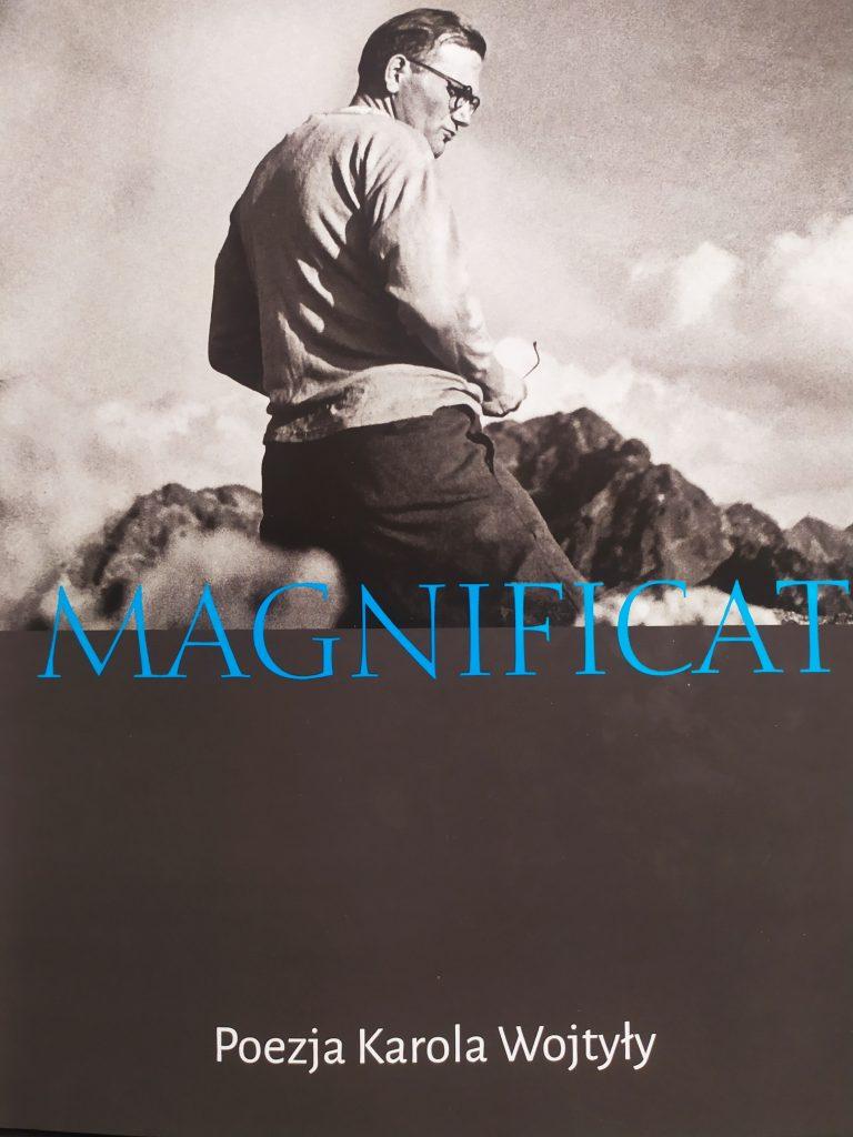 Mężczyzna w okularach. Widoczny napis - niebieskimi literami - Magnificat