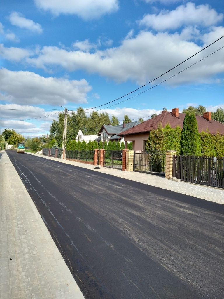 Droga asfaltowa, z lewej strony widoczne domy oraz chodnik.